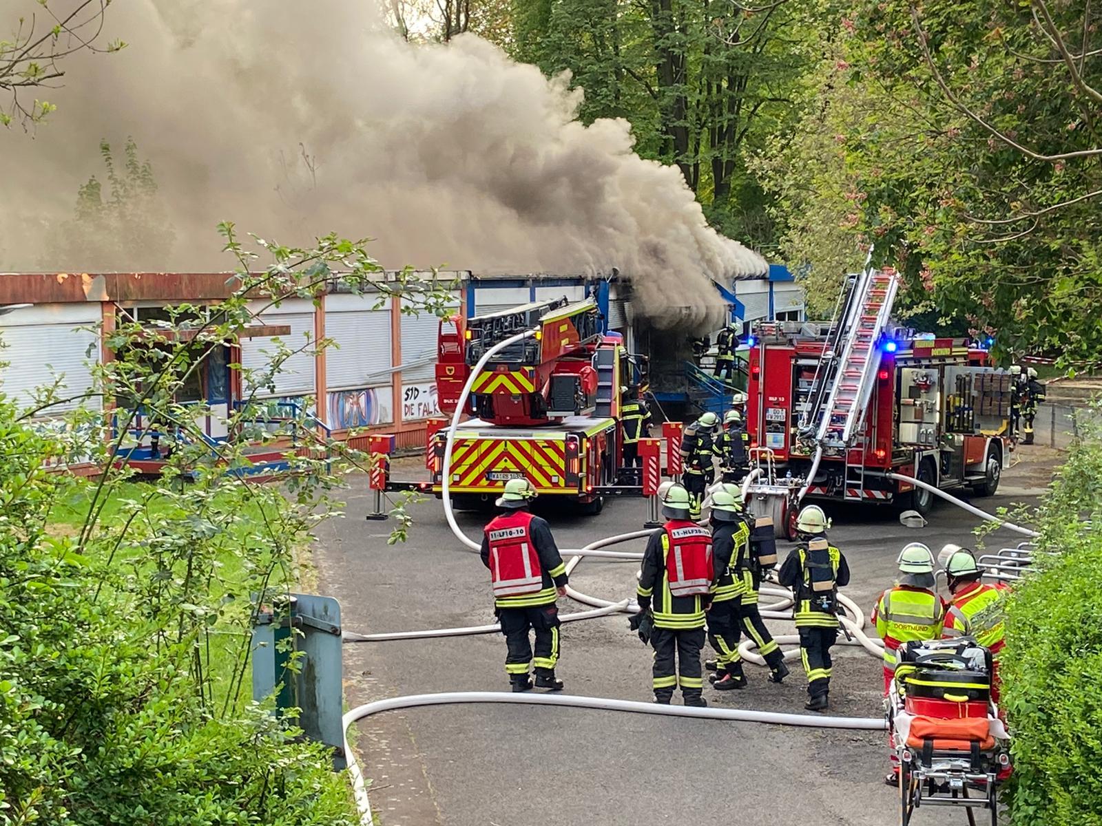 Feuerwehrleute besprechen sich während im Hintergrund Rauch aus einem Gebäude aufsteigt