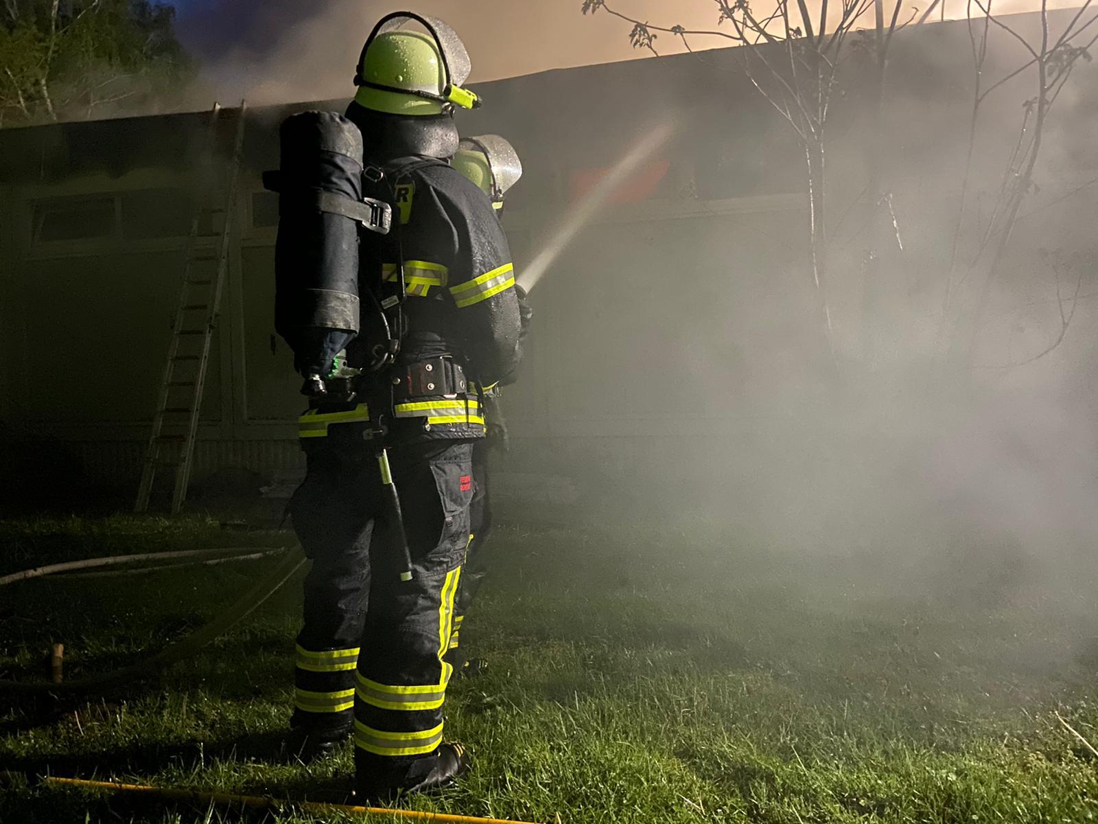 zwei Feuerwehrleute löschen im Dunkeln mit einem C-Strahlrohr ein stark verrauchtes Gebäude mit Flachdach